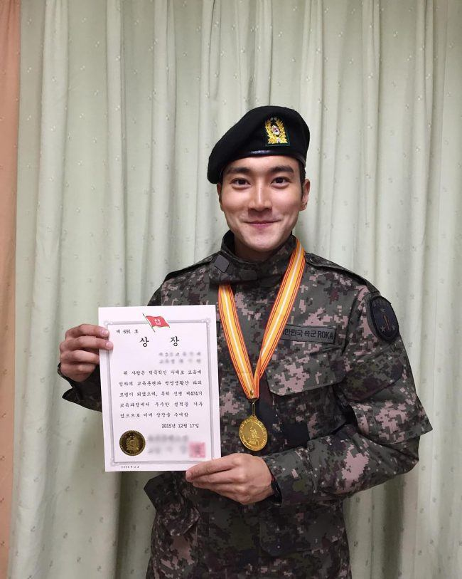 Siwon holding a certificate after his first month of training.